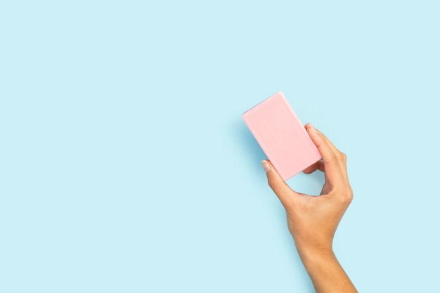 Woman hand holding a pink soap bar on a light blue background