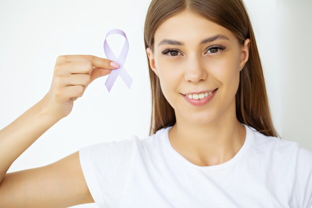 Woman hand holding purple ribbon bow, lupus lse or alzheimer awareness symbol.