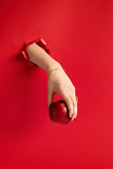 赤い紙の壁の穴から赤いリンゴを持っている女性の手