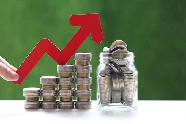 Женская рука, держащая график с красной стрелкой и стопку монет, денег в стеклянной бутылке на естественном зеленом фоне, инвестициях и бизнес-концепции