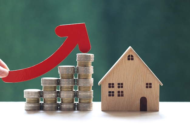 Woman hand holding red arrow graph and stack of coins money with model house on natural green background