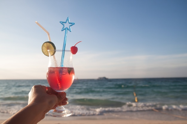 Woman hand holding red color glass of summer drink with beach