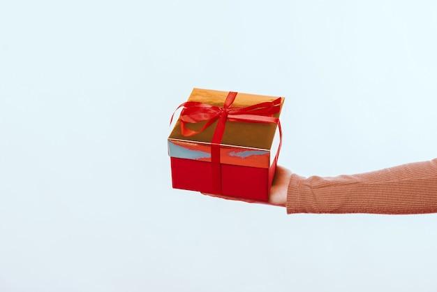 흰색 배경 위에 빨간색 선물 상자를 들고 여자 손