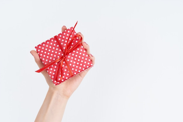 Woman hand holding red gift with ribbon, manicured hand with nail polish on white