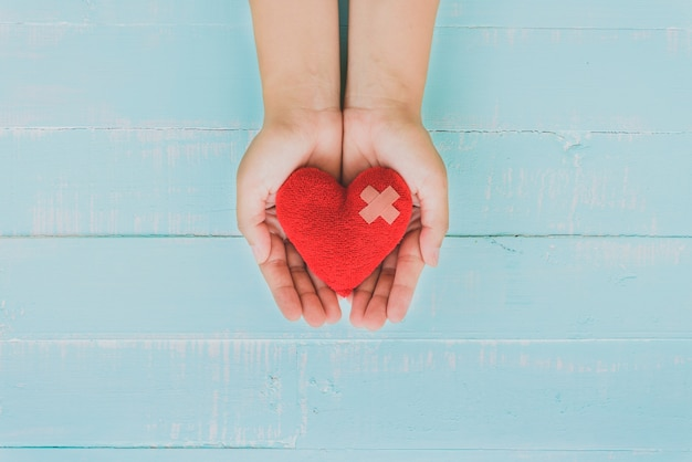 Woman hand holding red heart on blue wooden background