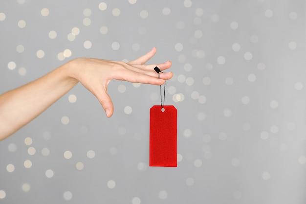 여자 손 defocus 조명으로 손가락에 빨간 가격표를 들고