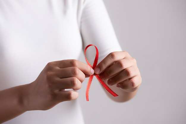 Woman hand holding red ribbon hiv, world aids day awareness
