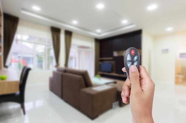 リモコンの家庭用警報システムを持っている女性の手。セキュリティシステム