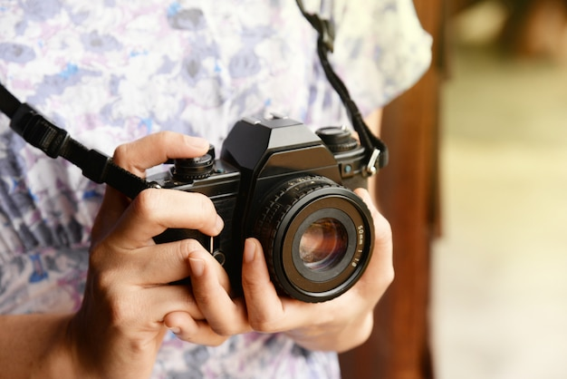 Woman hand holding retro camera close-up with copy space