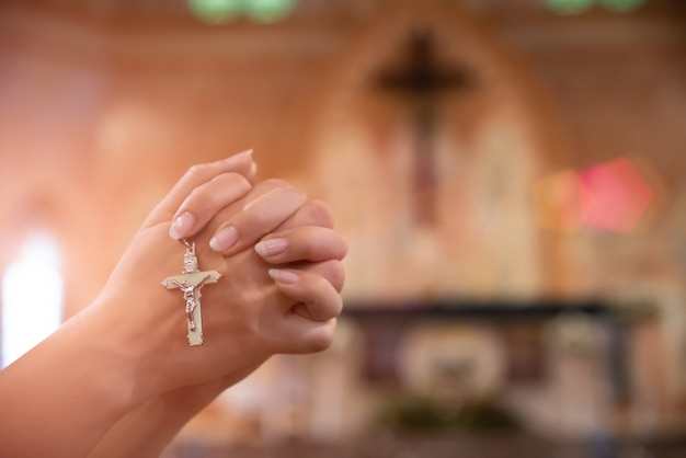 Woman hand holding rosary against cross and praying to god at church