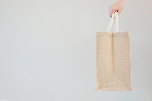 Woman hand holding sackcloth shopping bag