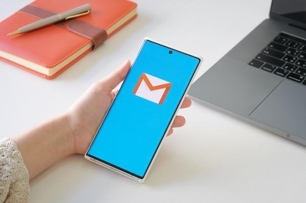 携帯電話6sモバイルで表示されているgmailアプリの手前の画面を持っている女性。 gmailはグーグルが提供する無料のメールサービスです
