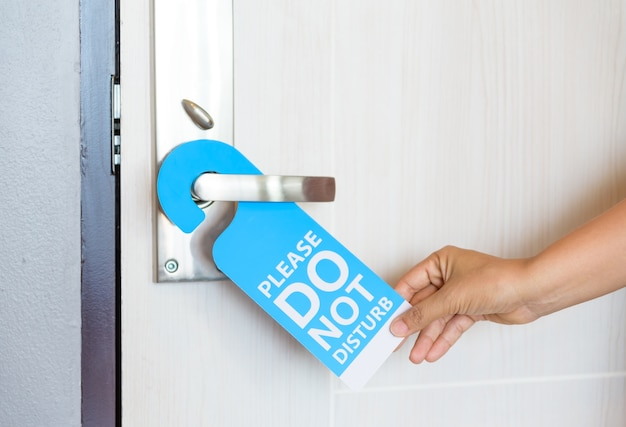 Woman hand holding signboard do not disturb hanging on the door