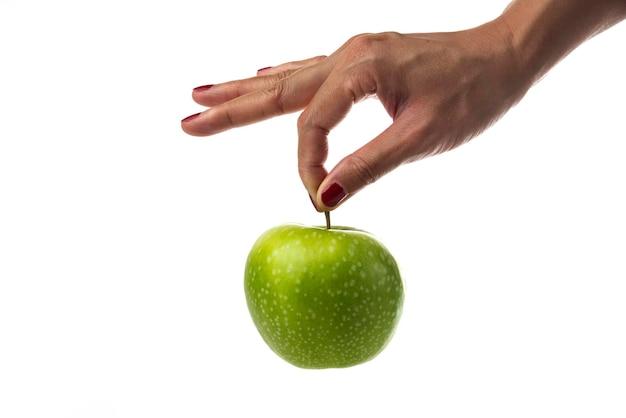 Mano della donna che tiene singola mela su bianco.