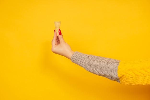 노란색 배경에 고립 된 작은 빈 바삭한 아이스크림 콘을 들고 여자 손