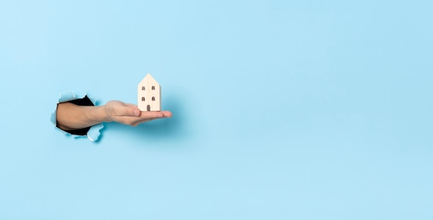 파란색 종이 배경에 구멍을 통해 작은 집을 들고 여자 손. 보험 및 판매 홈 개념입니다.