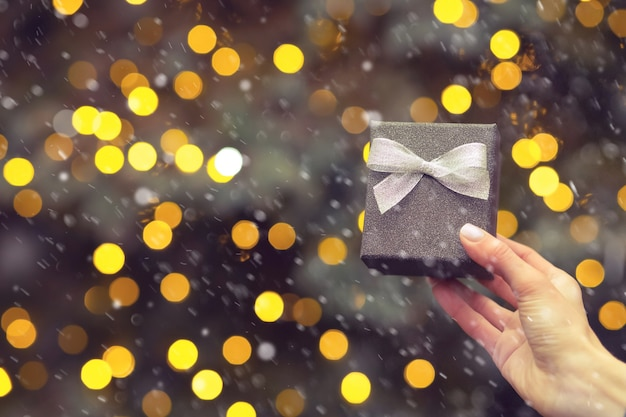 Woman hand holding a small silver gift box with a bow at the background of christmas tree during the snowfall. empty space