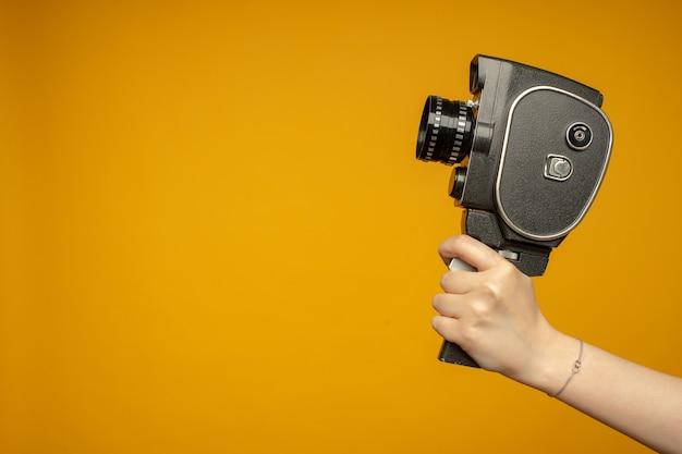 여자 손을 잡고 작은 비디오 오래 된 레트로 블랙 카메라 8mm 흰색 배경에 고립