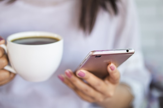 Woman hand holding smart phone and drinking coffee