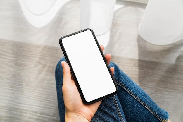 スマートフォンと画面を持っている女性の手は空白、ソーシャルネットワークの概念です。