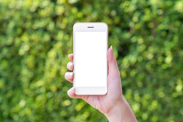 ぼやけた葉背景にスマートフォンを持つ女性の手