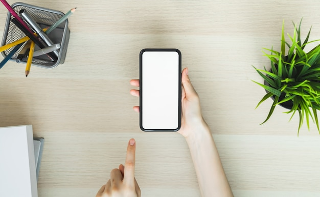 Woman hand holding smartphone and touching blank screen. mockup of advertisement.