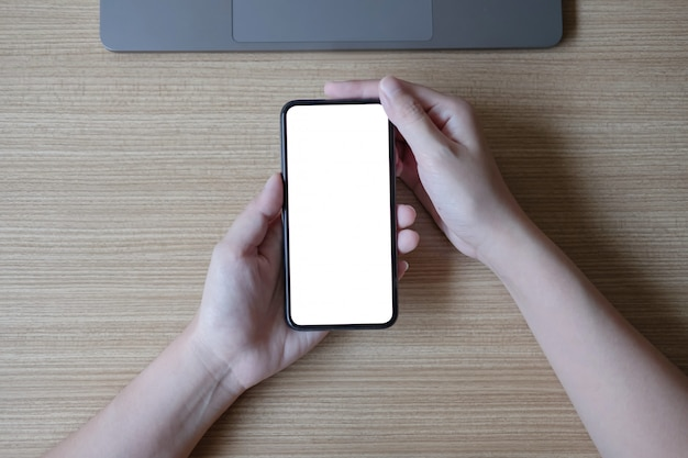 Woman hand holding smartphone with blank white screen on workplace