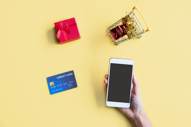 黄色の背景にクレジットカードでスマートフォンを持っている女性の手。オンラインショッピングのコンセプト。