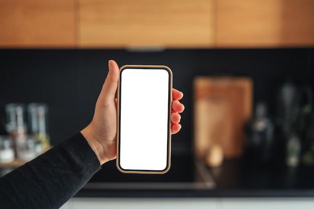自宅のキッチンで垂直の白い画面でスマートフォンを持っている女性の手