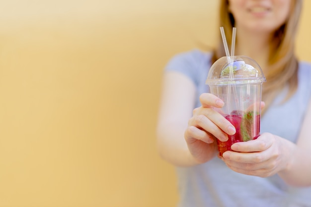 Woman hand holding smoothie shake against colored wall.