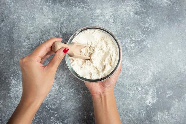 Cucchiaio della holding della mano della donna all'interno della ciotola della farina.
