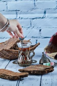 Mano della donna che tiene un cucchiaio di tè e vari dolci sulla tavola di legno blu
