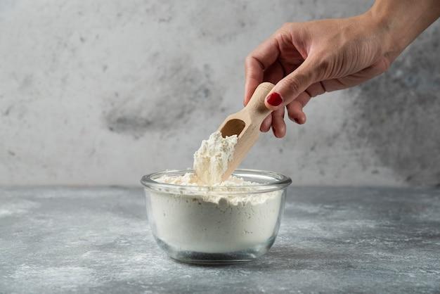 Cucchiaio della holding della mano della donna sopra la ciotola della farina.