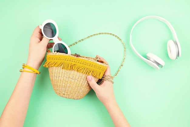 Woman hand holding straw bag with summer vacations accessories. summer holidays, travel to tropical countries, seaside, summertime style concept. top view, flat lay