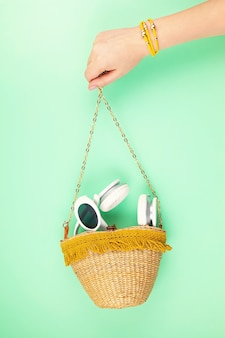 Woman hand holding straw bag with summer vacations accessories. summer holidays, travel to tropical countries, seaside, summertime style concept.