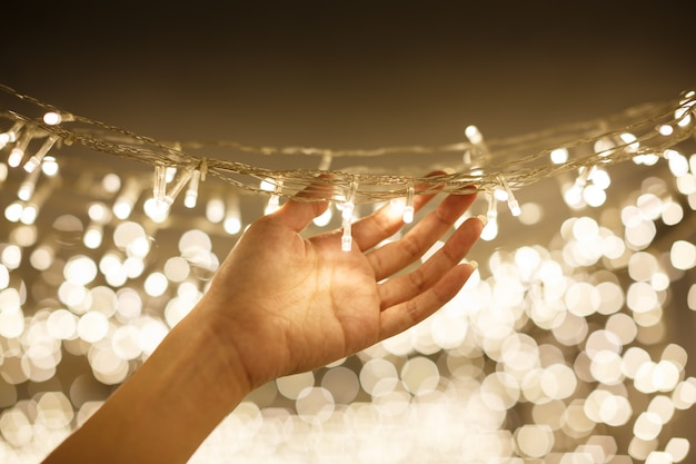 Woman hand holding string vintage warm led christmas lights with blurred and bokeh background