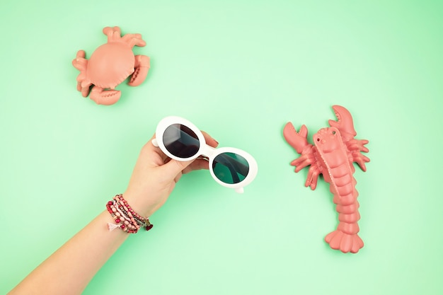 Woman hand holding stylish sunglasses. summer holidays, vacation, summertime fashion style concept. top view. flat lay