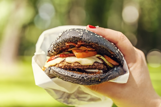 Woman hand holding tasty burger with black bread outdoors