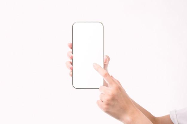 白い背景で隔離の空白の画面で黒いスマートフォンを持っている女性の手