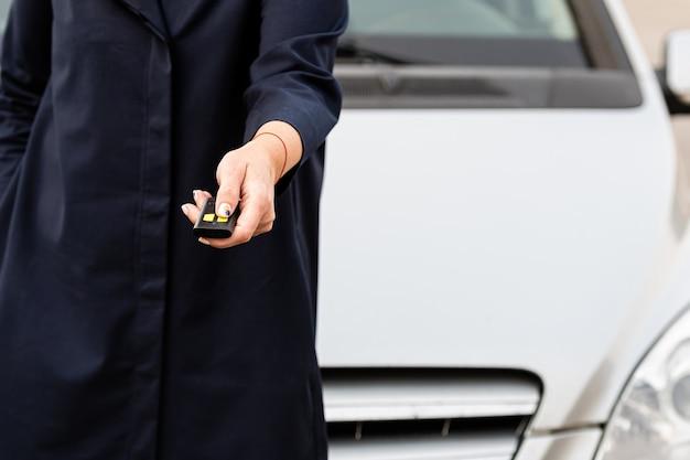 Женщина держит пульт от машины, он нажимает на пульт, чтобы открыть дверь машины
