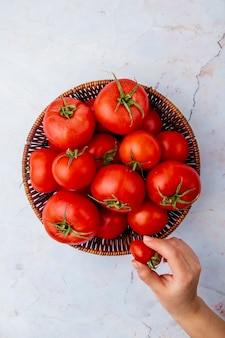 Woman hand holding tomato and basket of tomatoes on white surface