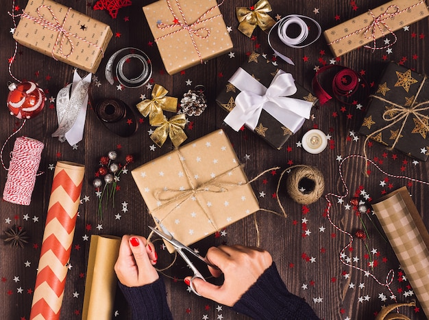 Woman hand holding twine rope with scissors for cutting and packaging christmas gift box