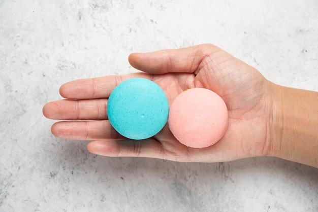 Woman hand holding two tasty macarons on marble surface.