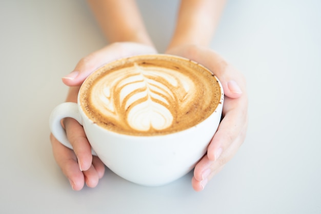Woman hand holding a white coffee mug.  coffee is a latte.