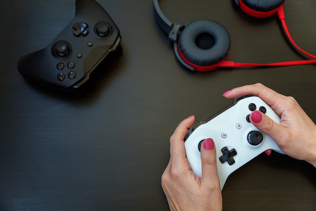Woman hand holding white joystick gamepad, game console isolated on black .