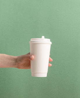 Woman hand holding white large takeaway paper coffee cup mock up on green background