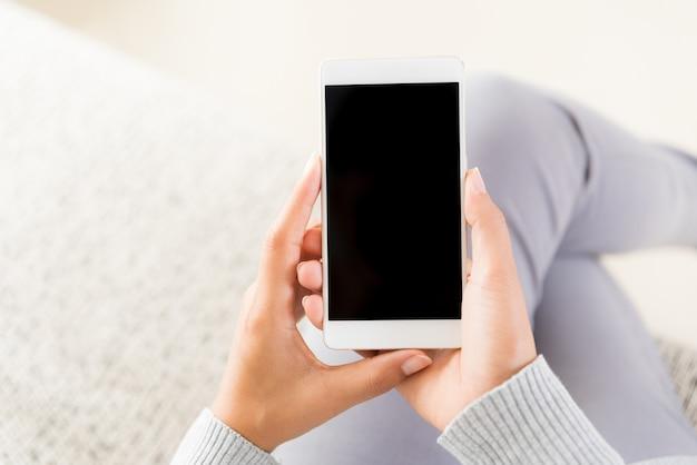 白い携帯電話を持ち、自宅のソファに座っている女性の手