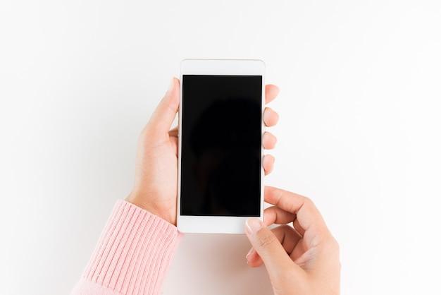 白いテーブルの背景に白い携帯電話スマートフォンを持っている女性の手