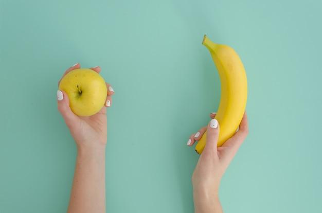 Woman hand holding yellow small apple and tropical banana