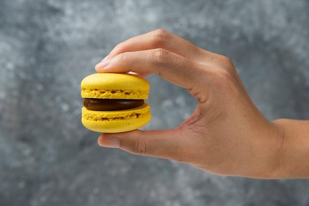 Женщина рука желтого вкусного macaron на мраморной поверхности.